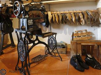 atelier de cordonnerie, avec machine à coudre de cordonnier en premier plan et assortiment de formes pour la confection de chaussures