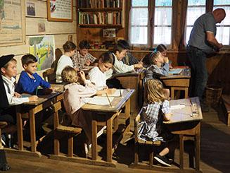 classe avec tables anciennes, carte de géographie accrochées aux murs, des enfants sont assis à leur place