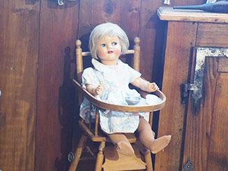 Jolie poupée ancienne assise dans une chaise haute avec tablette en bois
